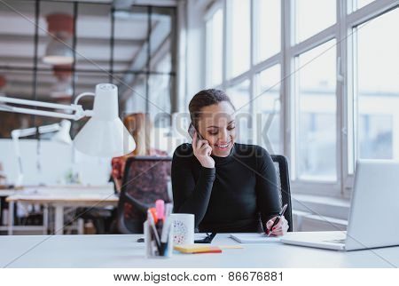Happy Young Woman Taking Notes While Talking On Mobile Phone