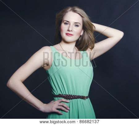 Beautiful Blond Girl With Blue Eyes In The Green Dress Smiling On A Dark Background
