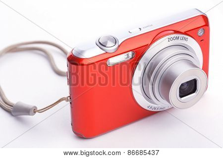red compact zoom digital camera over white