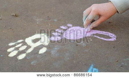Girl drawing with colored chalk on the pavement