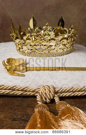 Royal scepter and golden crown on a cream cushion