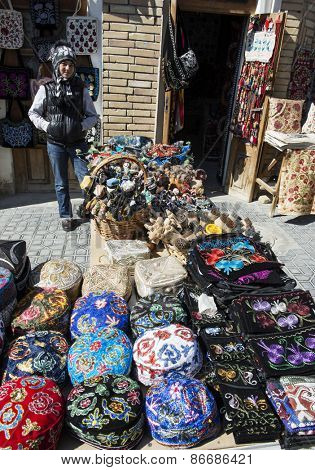 BUKHARA, UZBEKISTAN - MARCH 16, 2015: Gift shop. Giirl sells national headgear - the skullcap.