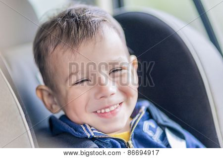 Portrait Of Young Caucasian Happy Little Boy Sitting On A Car Safety Seat