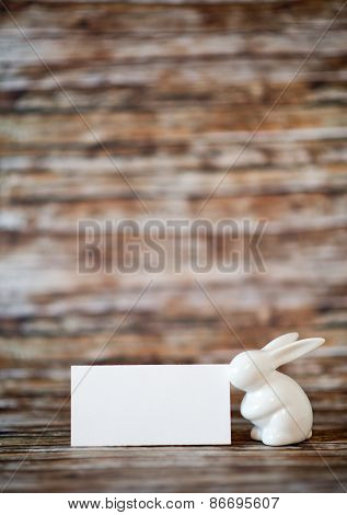 Close up Easter Bunny Figurine with Blank White Greeting Card on Top of a Wooden Table with Blurry Background, Emphasizing Copy Space.