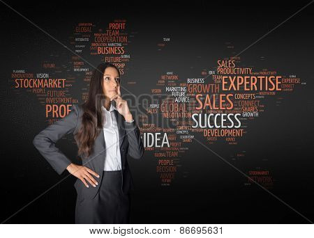 Young Thoughtful Businesswoman in Front a World Map in a Word Tag Cloud Design While Looking up.
