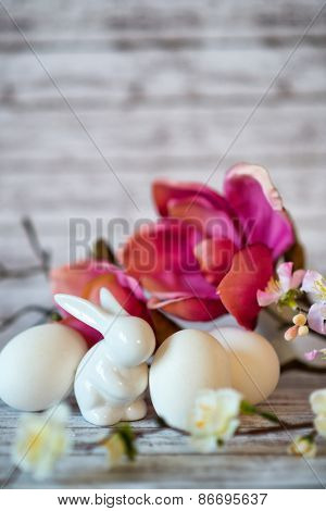 Small White Rabbit Figurine with White Easter Eggs and Pink Orchids and Blossoms on Rustic Wooden Background
