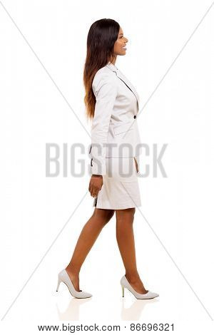 side view of young african american businesswoman walking on white background