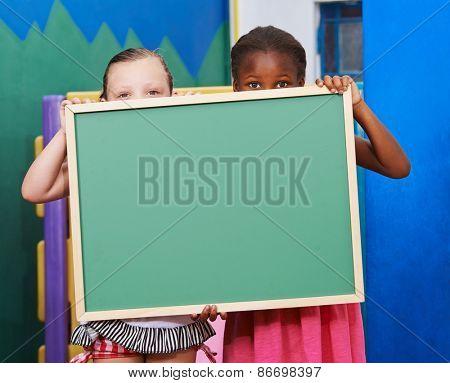 Two children hiding behind an empty chalkboard in kindergarten