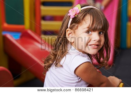 Smiling girl playing happily in a kindergarten