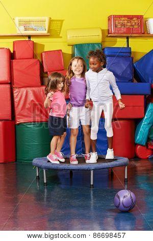 Three children jumping on trampoline together in gym of a kindergarten
