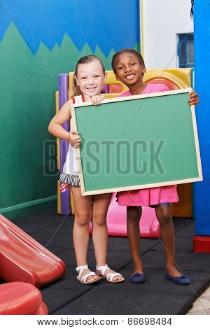 Two happy children holding an empty blackboard in kindergarten