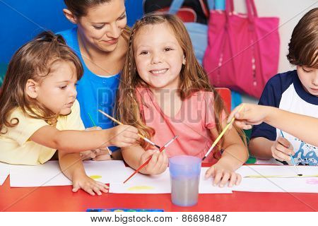 Art teacher and children painting images together in elementary school