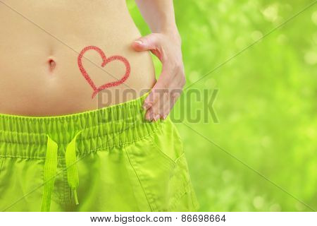 Woman's fit belly with heart and athletic pants,on green bokeh background