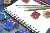 stock photo of sketch book  - Used water color paint pencil and paintbrush on white sketch book - JPG