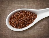 stock photo of spooning  - Flax seeds in white porcelain spoon  - JPG