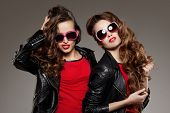picture of friendship  - Sisters twins in hipster sun glasses laughing Two fashion models Women smiling positive Friends group having fun - JPG