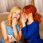 picture of sisters  - Two sisters a blonde and a redhead listening to music on headphones - JPG