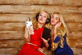 stock photo of sisters  - Two sisters blonde listening to music on headphones - JPG