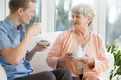 image of male nurses  - Elder woman and male nurse drinking coffee - JPG