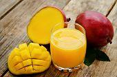 foto of mango  - mango juice and fresh mango on a dark wood background - JPG