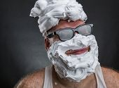 stock photo of shaved head  - Strange smiling man in glasses with shaving foam on his face and on his head closeup - JPG