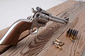 stock photo of revolver  - A revolver on a piece of wood. ** Note: Shallow depth of field - JPG