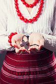 stock photo of rosary  - beautiful young woman wearing national ukrainian clothes and praying with rosary in hands  - JPG