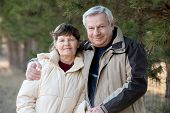 foto of wifes  - Portrait of elder couple on a walk in park senior man hugging his wife with gentleness - JPG