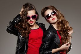 foto of rocking  - Sisters twins in hipster sun glasses laughing Two fashion models Women smiling positive Friends group having fun - JPG