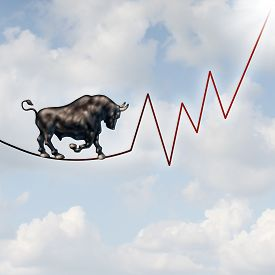 stock photo of risk  - Bull market risk financial concept as a heavy bullish beast walking on a high tightrope shaped as a stock market profit chart representing the investment danger ahead - JPG