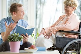 stock photo of handicapped  - Male care assistant reading senior woman book - JPG