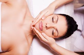 stock photo of therapist  - Top view of beautiful young woman lying on back while massage therapist massaging her face - JPG