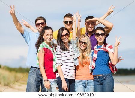 summer holidays, vacation, tourism, travel and people concept - group of happy friends having fun and showing victory gesture on beach