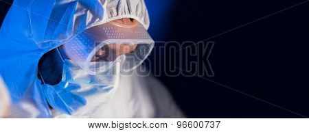 science, chemistry, biology, medicine and people concept - close up of scientist face in goggles and protective mask at chemical laboratory over dark background