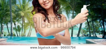 people, tanning, skincare, summer and travel concept - happy young woman in bikini swimsuit applying sunscreen to her arm skin over tropical beach with palm trees and pool at hotel resort background