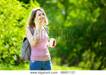Woman talking on the phone holding a takeaway coffee cup and smiling.