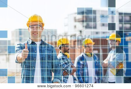 business, building, teamwork, gesture and people concept - group of smiling builders in hardhats showing thumbs up outdoors over blue squared grid background