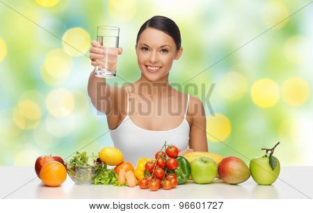 people, diet and vegetarian concept - happy asian woman with healthy food showing glass of water over green lights background