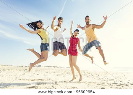 Group of friends making a jump together at the beach