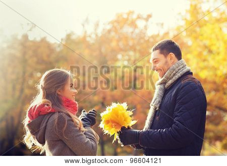 love, relationship, family, season and people concept - smiling couple with bunch of leaves in autumn park
