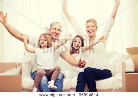 family, children, accomodation and home concept - smiling parents and two little girls waving hands at new home