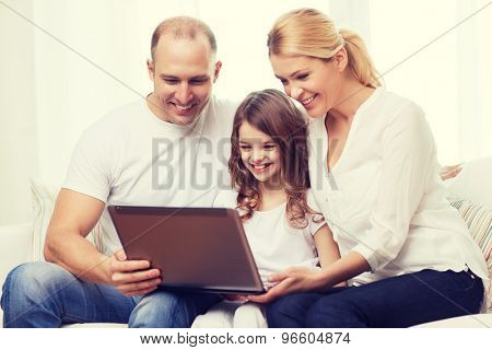family, child, technology and home concept - smiling parents and little girl with laptop at home
