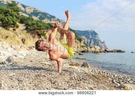 Happy guy on the beach holding a finger up in the unusual position
