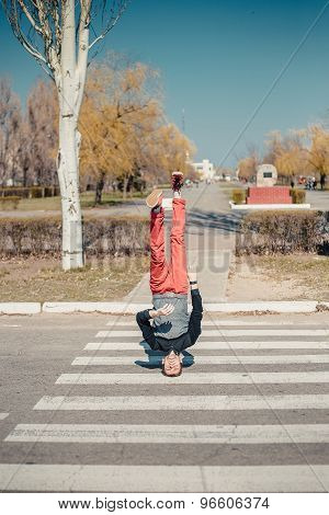 Healthy young man goes on a pedestrian crossing on the head