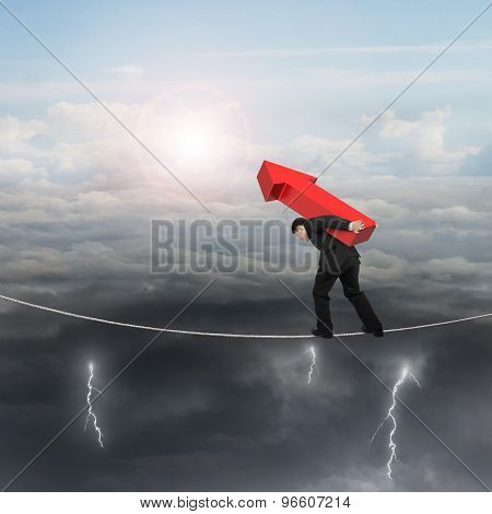 Businessman Carrying Red Arrow Sign Balancing On Tightrope