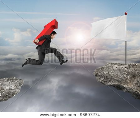 Jumping Businessman Carrying Arrow Up Sign To Flag On Cliff