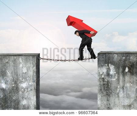 Businessman Carrying Red Arrow Sign Balancing On Rusty Chain