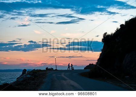 Young couple with tandem bicycle at sea coast after sunset