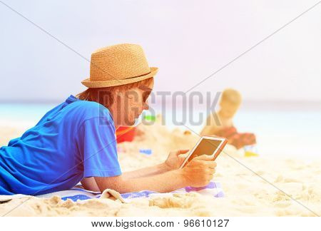 father looking at touch pad while son play on beach