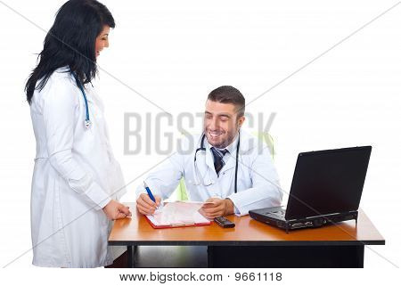 Two Doctors Having Conversation In Office